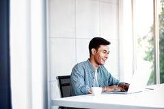 Ευτυχής νέος επιχειρηματίας που εργάζεται στο lap-top υπολογιστών στην αρχή στοκ φωτογραφία