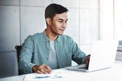Ευτυχής νέος επιχειρηματίας που εργάζεται στο lap-top υπολογιστών στοκ εικόνες