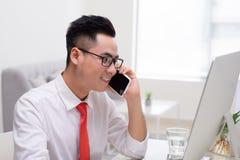 Ευτυχής νέος επιχειρηματίας που μιλά στο τηλέφωνο κυττάρων και που χρησιμοποιεί τον υπολογιστή Στοκ φωτογραφία με δικαίωμα ελεύθερης χρήσης