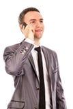 Ευτυχής νέος επιχειρηματίας που μιλά στο τηλέφωνο και που ανατρέχει Στοκ Εικόνες