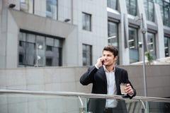 Ευτυχής νέος επιχειρηματίας που μιλά στο τηλέφωνο κυττάρων και τον καφέ κατανάλωσης Στοκ Φωτογραφίες