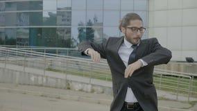 Ευτυχής νέος επιχειρηματίας στο κοστούμι και δεσμός που φορά τον αστείο χορό γυαλιών χαρωπά στη φύση μπροστά από την εταιρία - απόθεμα βίντεο