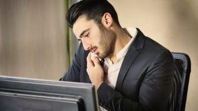 Ευτυχής νέος επιχειρηματίας στο τηλέφωνο, που κάθεται στο γραφείο Στοκ φωτογραφία με δικαίωμα ελεύθερης χρήσης