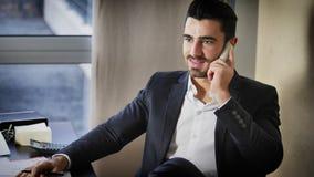 Ευτυχής νέος επιχειρηματίας στο τηλέφωνο, που κάθεται στο γραφείο Στοκ Φωτογραφία