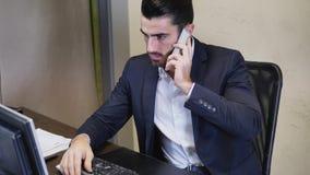 Ευτυχής νέος επιχειρηματίας στο τηλέφωνο, που κάθεται στο γραφείο Στοκ φωτογραφίες με δικαίωμα ελεύθερης χρήσης
