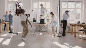 Ευτυχής νέος μαύρος εργαζόμενος γραφείων θηλυκών που χορεύει με τους  φιλμ μικρού μήκους