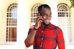 Ευτυχής νέος μαύρος τύπος που μιλά στο τηλέφωνο κυττάρων Στοκ φωτογραφία με δικαίωμα ελεύθερης χρήσης