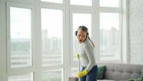 Ευτυχής νέος ξανθός κάνει τα οικιακά και έχοντας τη διασκέδαση στο σύγχρονο σπίτι, πλένει το πάτωμα με τη σφουγγαρίστρα, το τραγο απόθεμα βίντεο