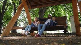 Ευτυχής νέος οικογενειακός πατέρας, μητέρα, γιος και λίγη κόρη που οδηγούν σε μια ταλάντευση στο πάρκο Γέλιο και χαμόγελο 4K αργό απόθεμα βίντεο