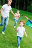 ευτυχής νέος πατέρας με το παιχνίδι κορών και γιων με τον ικτίνο στοκ φωτογραφία με δικαίωμα ελεύθερης χρήσης