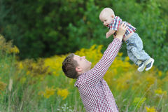 Ευτυχής νέος πατέρας που ανυψώνει επάνω το γιο του Στοκ εικόνα με δικαίωμα ελεύθερης χρήσης