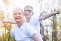 Ευτυχής νέος πατέρας που φέρνει το γιο του στην πλάτη Στοκ εικόνα με δικαίωμα ελεύθερης χρήσης