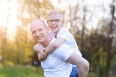 Ευτυχής νέος πατέρας που φέρνει το γιο του στην πλάτη Στοκ φωτογραφίες με δικαίωμα ελεύθερης χρήσης