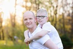 Ευτυχής νέος πατέρας που φέρνει το γιο του στην πλάτη Στοκ εικόνες με δικαίωμα ελεύθερης χρήσης
