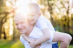 Ευτυχής νέος πατέρας που φέρνει το γιο του στην πλάτη Στοκ φωτογραφία με δικαίωμα ελεύθερης χρήσης