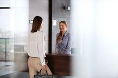 Ευτυχής νέος ρεσεψιονίστ που μιλά με τη επιχειρηματία στην αρχή Στοκ Εικόνες