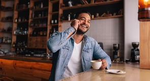 Ευτυχής νέος τύπος στον καφέ που μιλά στο τηλέφωνο Στοκ εικόνα με δικαίωμα ελεύθερης χρήσης