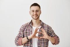 Ευτυχής να είναι ερωτευμένος με σας Πυροβολισμός στούντιο του όμορφου συνηθισμένου τύπου στα γυαλιά που παρουσιάζουν σημάδι καρδι στοκ εικόνα με δικαίωμα ελεύθερης χρήσης