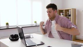 Ευτυχής νεαρός άνδρας με το lap-top στο γραφείο απόθεμα βίντεο
