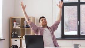 Ευτυχής νεαρός άνδρας με το lap-top στο γραφείο φιλμ μικρού μήκους
