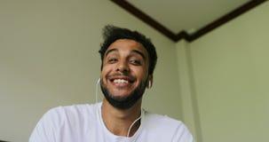 Ευτυχής νεαρός άνδρας που έχει την τηλεοπτική κλήση συνομιλίας, λατινικά ακουστικά ένδυσης τύπων που μιλά on-line, άποψη οθονών υ φιλμ μικρού μήκους