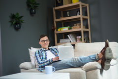 Ευτυχής νεαρός άνδρας που βρίσκεται στον καναπέ, που λειτουργεί στο lap-top Στοκ φωτογραφία με δικαίωμα ελεύθερης χρήσης