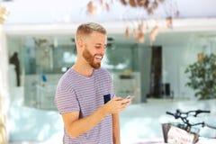 Ευτυχής νεαρός άνδρας που εξετάζει το κινητό τηλέφωνο Στοκ Εικόνα