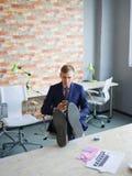 Ευτυχής νεαρός άνδρας που εργάζεται στο γραφείο στην επίσημη μπλε επιχειρησιακή έννοια κοστουμιών Στοκ εικόνα με δικαίωμα ελεύθερης χρήσης
