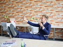 Ευτυχής νεαρός άνδρας που εργάζεται στο γραφείο στην επίσημη μπλε επιχειρησιακή έννοια κοστουμιών Στοκ Φωτογραφία