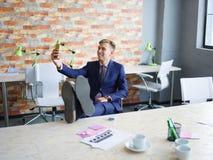 Ευτυχής νεαρός άνδρας που εργάζεται στο γραφείο στην επίσημη μπλε επιχειρησιακή έννοια κοστουμιών Στοκ φωτογραφίες με δικαίωμα ελεύθερης χρήσης