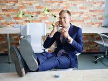 Ευτυχής νεαρός άνδρας που εργάζεται στο γραφείο στην επίσημη μπλε επιχειρησιακή έννοια κοστουμιών Στοκ Εικόνες