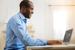 Ευτυχής νεαρός άνδρας που εργάζεται στο lap-top του Στοκ Φωτογραφία