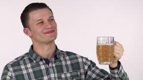Ευτυχής νεαρός άνδρας που κοιτάζει μακριά ονειρεμένα, που κρατά την κούπα της εύγευστης μπύρας απόθεμα βίντεο