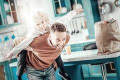 Ευτυχής νεαρός άνδρας που κρατά το γιο στην πλάτη του στοκ φωτογραφία με δικαίωμα ελεύθερης χρήσης