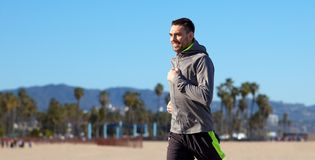 Ευτυχής νεαρός άνδρας που τρέχει πέρα από την παραλία της Βενετίας στοκ εικόνες με δικαίωμα ελεύθερης χρήσης