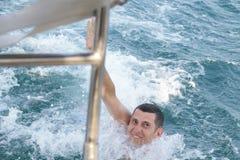 Ευτυχής νεαρός άνδρας στην μπλε θάλασσα στοκ εικόνες