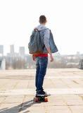 Ευτυχής νεαρός άνδρας ή έφηβος που οδηγά στο longboard Στοκ φωτογραφία με δικαίωμα ελεύθερης χρήσης