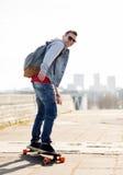 Ευτυχής νεαρός άνδρας ή έφηβος που οδηγά στο longboard Στοκ Εικόνες