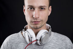 Ευτυχής νεαρός άνδρας με τα ακουστικά στο λαιμό του Στοκ Εικόνες