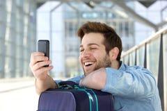 Ευτυχής νεαρός άνδρας με τη διακινούμενη τσάντα που εξετάζει το τηλέφωνο κυττάρων Στοκ Φωτογραφία