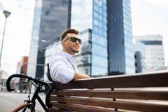 Ευτυχής νεαρός άνδρας με τη συνεδρίαση ποδηλάτων στον πάγκο πόλεων Στοκ εικόνες με δικαίωμα ελεύθερης χρήσης