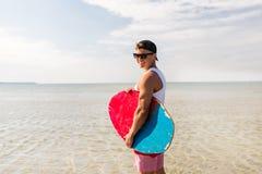 Ευτυχής νεαρός άνδρας με το skimboard στη θερινή παραλία Στοκ Εικόνες