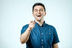 Ευτυχής νεαρός άνδρας πορτρέτου, γέλιο, που δείχνει με το δάχτυλο σε μερικοί Στοκ Φωτογραφία