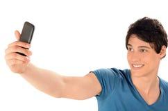 Ευτυχής νεαρός άνδρας που παίρνει μια φωτογραφία selfie με το έξυπνο τηλέφωνό του. Στοκ Εικόνες