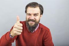 Ευτυχής νεαρός άνδρας που παρουσιάζει ΕΝΤΑΞΕΙ σημάδι με τον αντίχειρά του επάνω και που αναβοσβήνει στοκ εικόνες με δικαίωμα ελεύθερης χρήσης