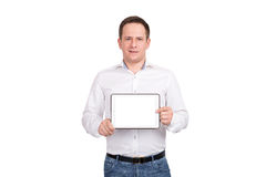 Ευτυχής νεαρός άνδρας που παρουσιάζει κενή οθόνη υπολογιστή ταμπλετών πέρα από το άσπρο υπόβαθρο εξέταση τη κάμερα Στοκ Φωτογραφία