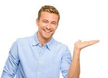 Ευτυχής νεαρός άνδρας που παρουσιάζει κενό copyspace στο άσπρο υπόβαθρο Στοκ φωτογραφία με δικαίωμα ελεύθερης χρήσης