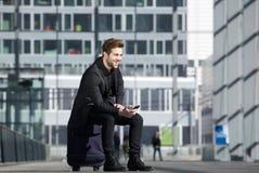 Ευτυχής νεαρός άνδρας που περιμένει στο σταθμό με το κινητό τηλέφωνο Στοκ Εικόνες