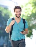 Ευτυχής νεαρός άνδρας που περπατά υπαίθρια με το κινητό τηλέφωνο Στοκ Εικόνα