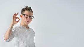 Ευτυχής νεαρός άνδρας που το ΕΝΤΑΞΕΙ σημάδι και το χαμόγελο Στοκ Φωτογραφίες